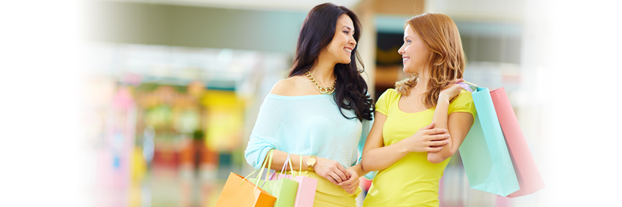 Two happy woman in mall holding shopping bags